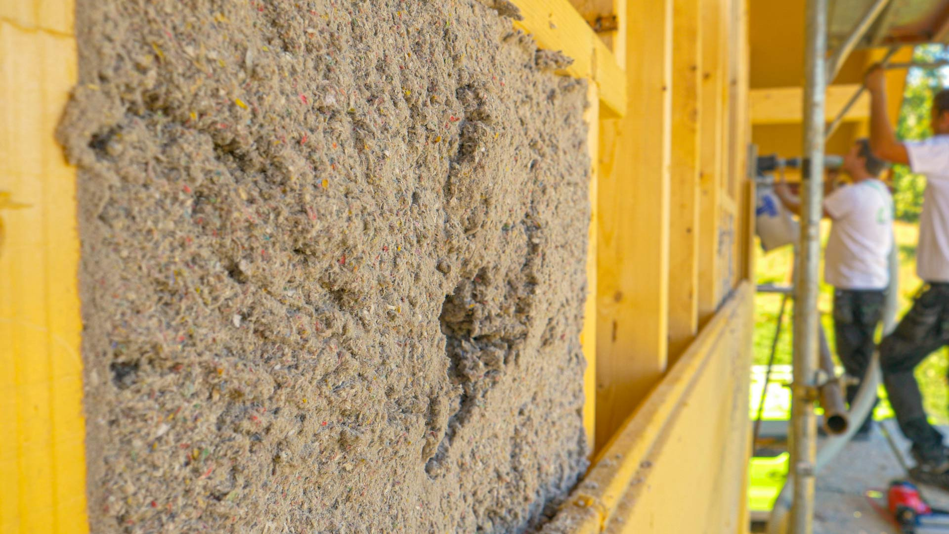 A group of workers blow cellulose insulation into the wooden walls